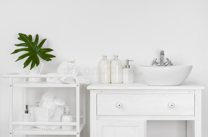 Badkamersbinnenland met witte muur, uitstekend meubilair, handdoeken en gootsteen stock foto
