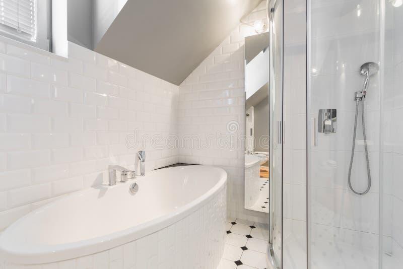 Badkar i det vita badrummet royaltyfri bild