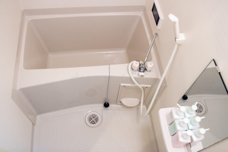 Badkar i ett litet badrum fotografering för bildbyråer