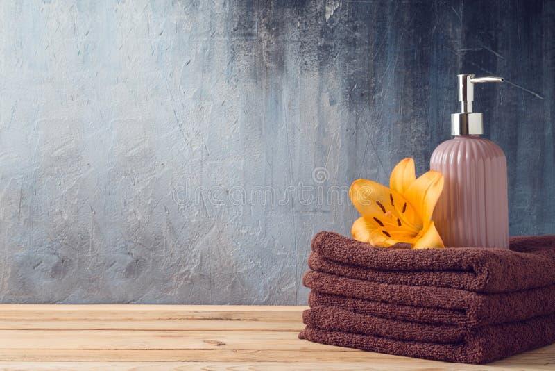 Badlakan och tvålflaska på trätabellen över badrumväggbakgrund fotografering för bildbyråer