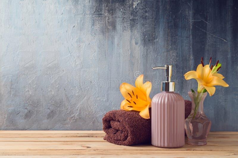 Badlakan och tvålflaska på trätabellen över badrumväggbakgrund royaltyfria bilder