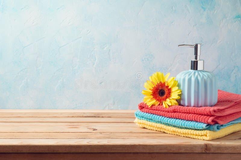 Badlakan och tvålflaska på trätabellen över badrumväggbakgrund arkivfoto