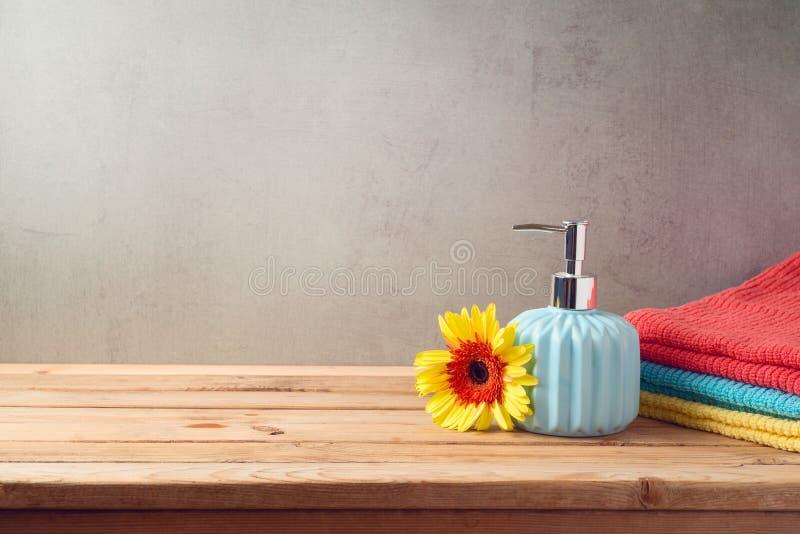 Badlakan och tvålflaska på trätabellen över badrumväggbakgrund arkivfoton
