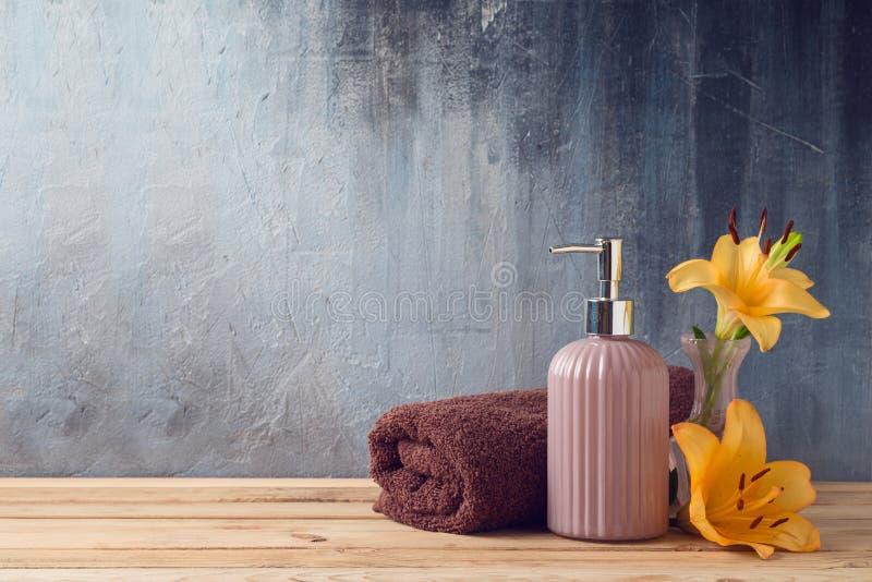 Badlakan och tvålflaska på trätabellen över badrumväggbakgrund arkivbilder