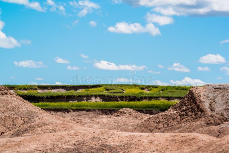Badlandsnationalpark - landskap med tre lager - grässlättar som eroderas för att vagga bildande och härlig blå himmel med pösig v royaltyfria foton