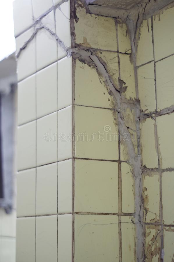 Badly fixed of breaking cracked pillar finishing with light yellow tiles. Badly fixed of breaking cracked pillar finishing with light yellow tile royalty free stock image
