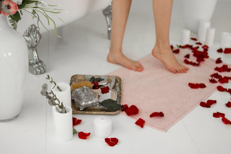 Badmat Benen op de deken na het bad Nam bloemblaadjes en kaarsen toe royalty-vrije stock foto