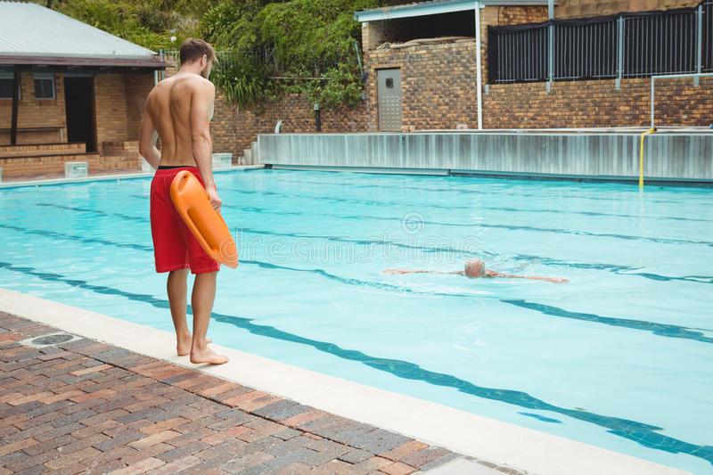Badmeester die in een zwembad die aan redding springen de hogere mens verdrinken stock afbeeldingen