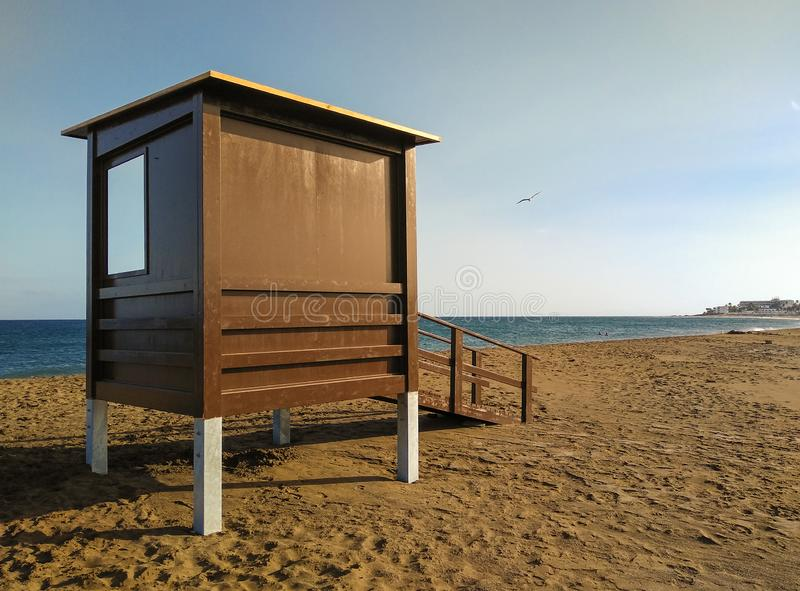 badmeesterhuis op het zand bij een vreedzaam strand zonder wacht of mensen die bij het zonsonderganguur zwemmen Achter de badmees royalty-vrije stock afbeeldingen