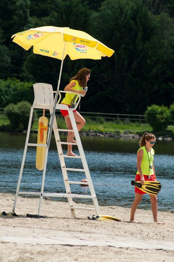 Badmeestermeisjes die op stoel met paraplu voor het meer zitten stock foto's