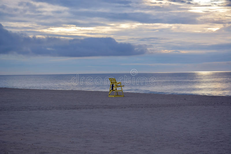 Badmeesterstoel op strand bij zonsopgang stock foto's