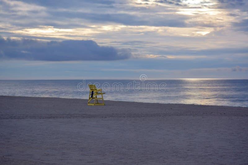 Badmeesterstoel op strand bij zonsopgang stock fotografie