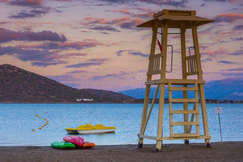 Badmeestertoren met boot bij de vreedzame golf van Elounda, Kreta stock afbeeldingen
