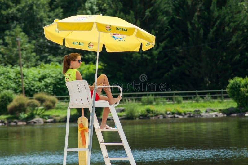 Badmeesterzitting op chaut met paraplu voor het meer op achtermening royalty-vrije stock afbeeldingen