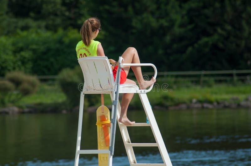Badmeesterzitting op stoel voor het meer op achtermening stock afbeeldingen