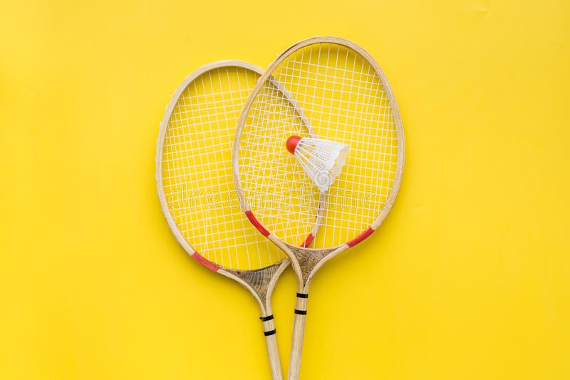 Badminton concept. Badminton rackets and shuttlecock on yellow background top view space for text royalty free stock photos