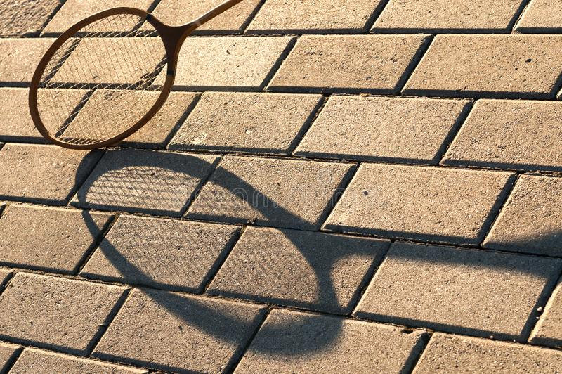 Badminton racket with shadow. Badminton racket and shadow on the stone walkway stock photography