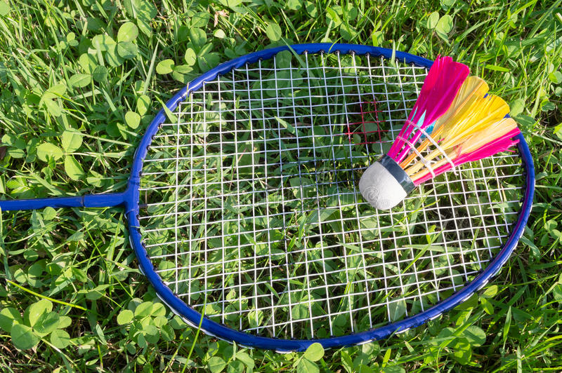 Badminton racket and shuttlecock on grass royalty free stock image