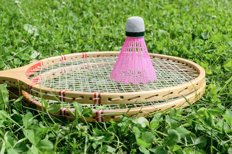 Badminton rackets and shuttlecock on grass royalty free stock photography
