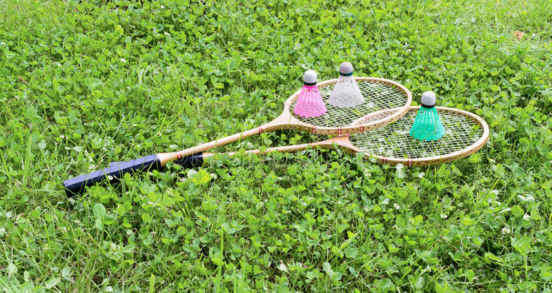 Badminton rackets and shuttlecocks on grass stock photography