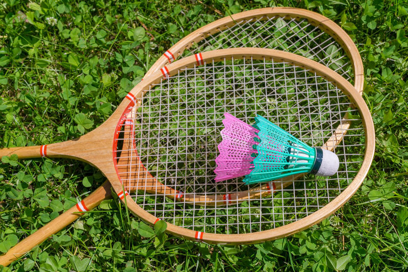 Badminton rackets and shuttlecocks on grass royalty free stock photos