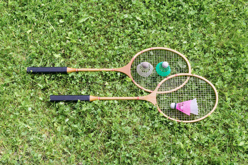 Badminton rackets and shuttlecocks on grass royalty free stock image