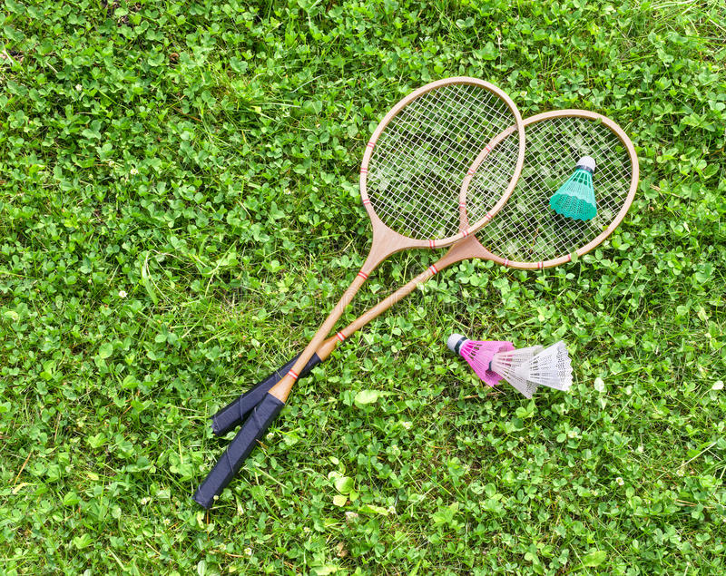 Badminton rackets and shuttlecocks on grass stock images