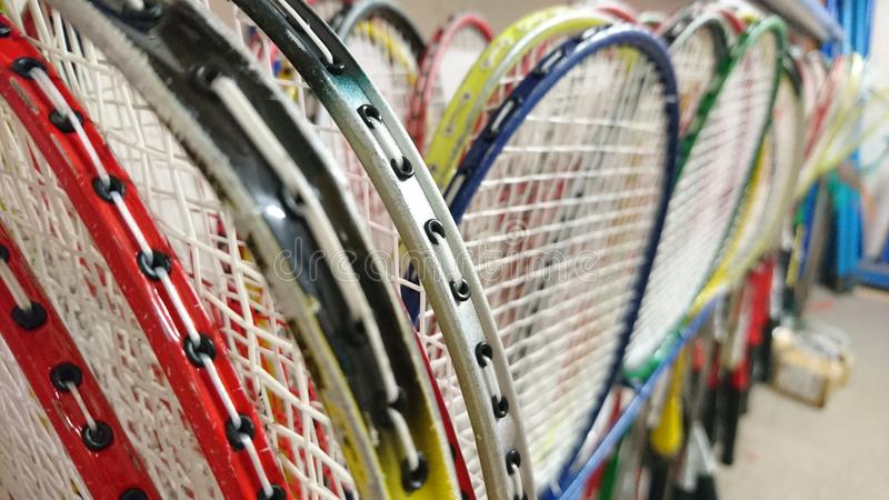Badminton rackets stored in games cupboard close up. Storage of rackets in room space along wall rack collection sport racquet handle grip squashed frame tightly royalty free stock photo