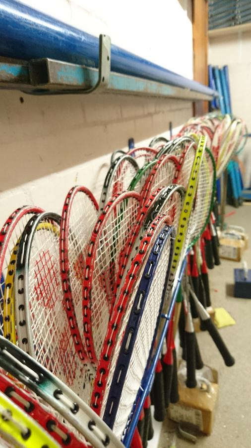 Badminton rackets stored in games cupboard. Storage of rackets in room sport racquet handle grip squashed frame tightly space along wall rack collection frames royalty free stock photo