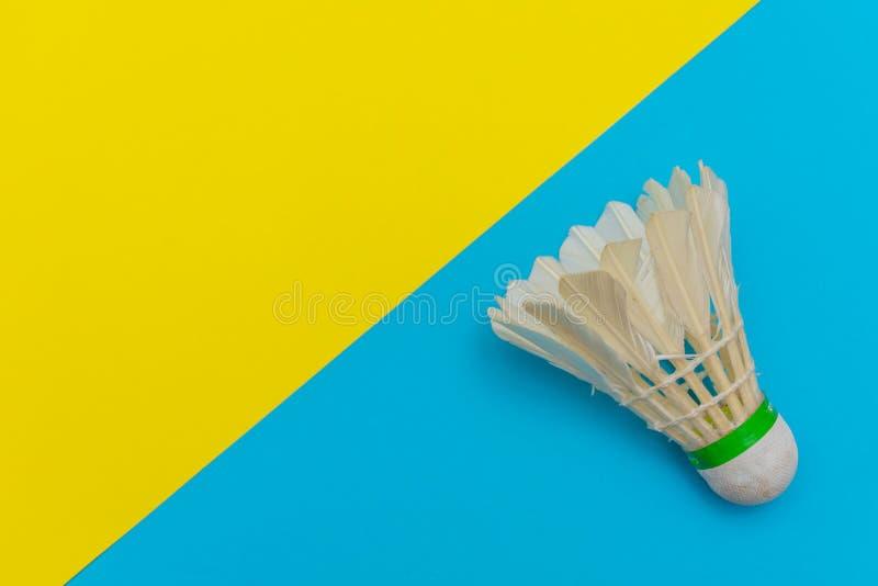 Badminton shuttlecock ou birdie em um plano azul brilhante sólido e amarelo plano de fundo que simboliza esportes e atividade com fotografia de stock