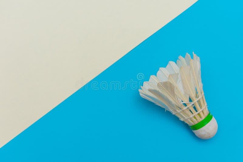 Badminton shuttlecock ou birdie em um plano azul e branco claro sólido que simboliza esportes e atividade com cópia imagens de stock royalty free