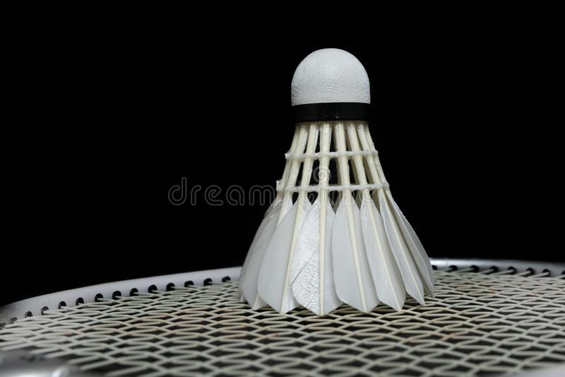 Badminton shuttlecock and racket on grass and black background stock photography