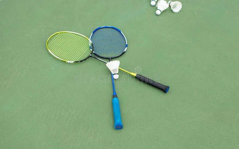 Badmintonbälle und -paddel auf einem Gericht stockfotografie