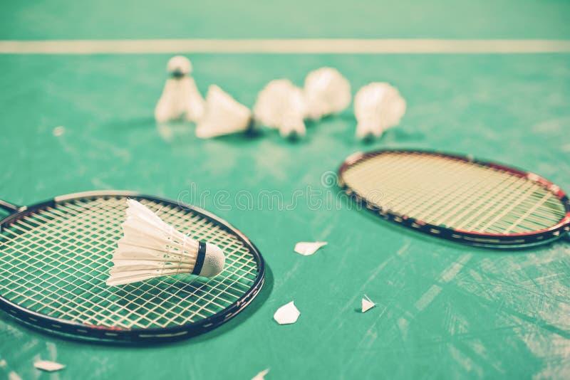 Badmintonbal & x28; shuttlecock& x29; en racket op hofvloer stock afbeeldingen