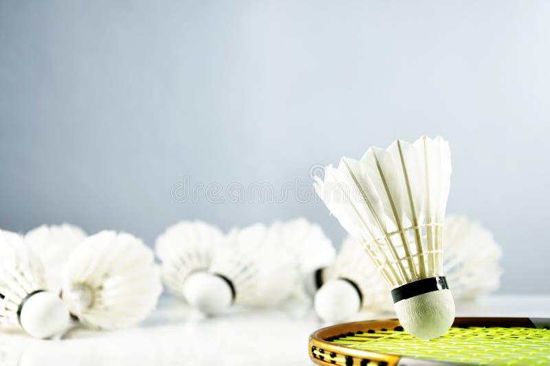 Badmintonbollfjäderboll och racket på golvet arkivfoto