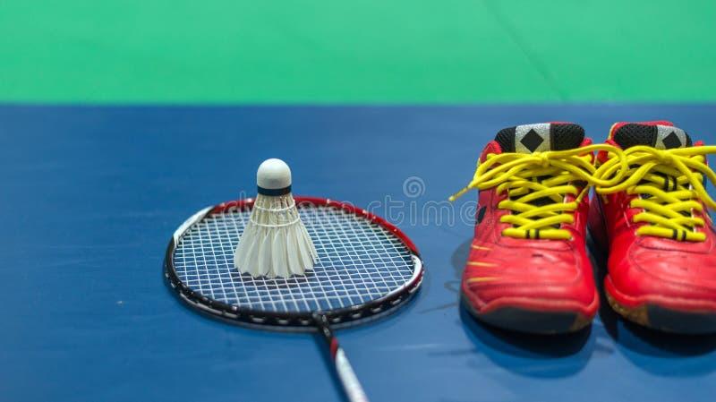 badmintonfjäderboll med racket och röda skor på domstolen royaltyfri bild