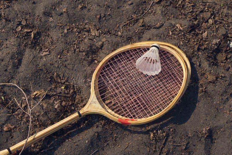 Badmintonracket och fjäderboll som ligger på jordning fotografering för bildbyråer