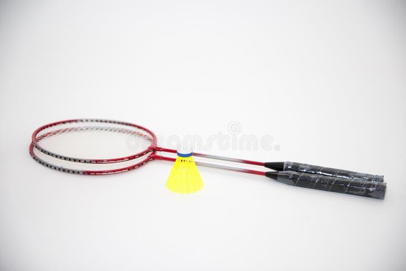 Badmintonracket och fjäderbollar på vit royaltyfri bild
