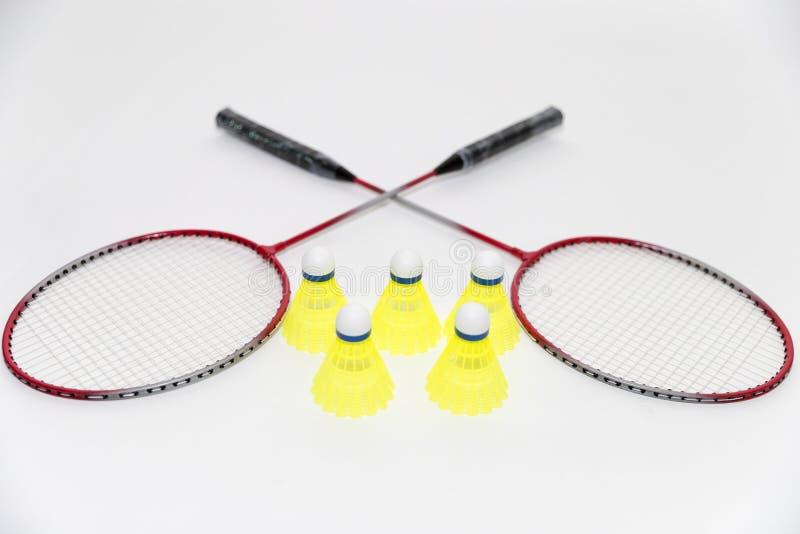 Badmintonracket och fjäderbollar på vit fotografering för bildbyråer