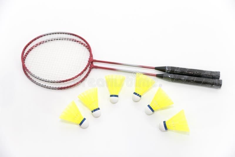 Badmintonracket och fjäderbollar på vit royaltyfri foto