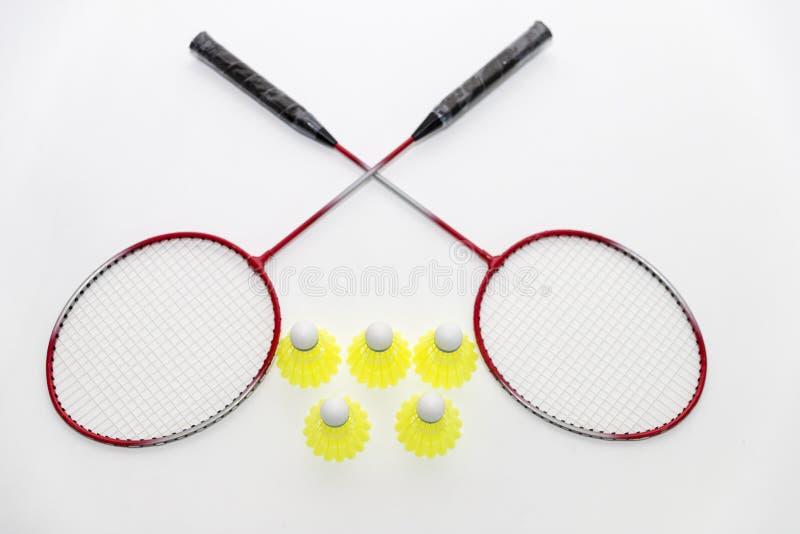 Badmintonracket och fjäderbollar på vit royaltyfri fotografi