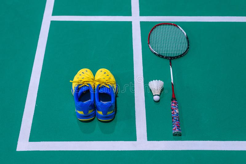 Badmintonschuhe mit Federball und Schläger auf Gericht lizenzfreie stockfotografie