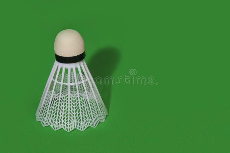 Badmintonshuttle op de groene achtergrond wordt geïsoleerd die royalty-vrije stock afbeelding