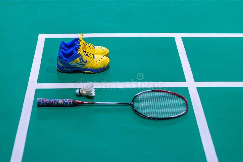 badmintonskor med fjäderboll och racket på domstolen royaltyfri bild
