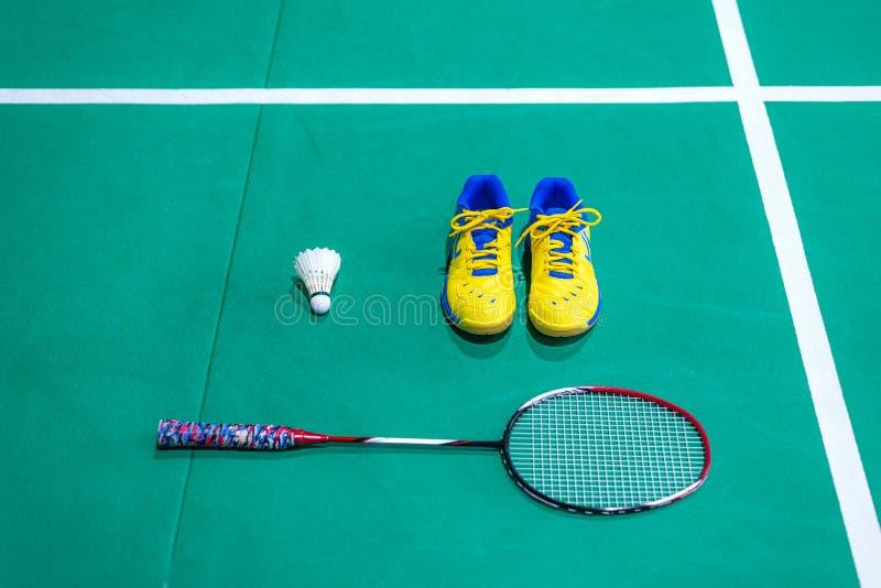 badmintonskor med suddig fjäderboll och racket på domstolen royaltyfri bild