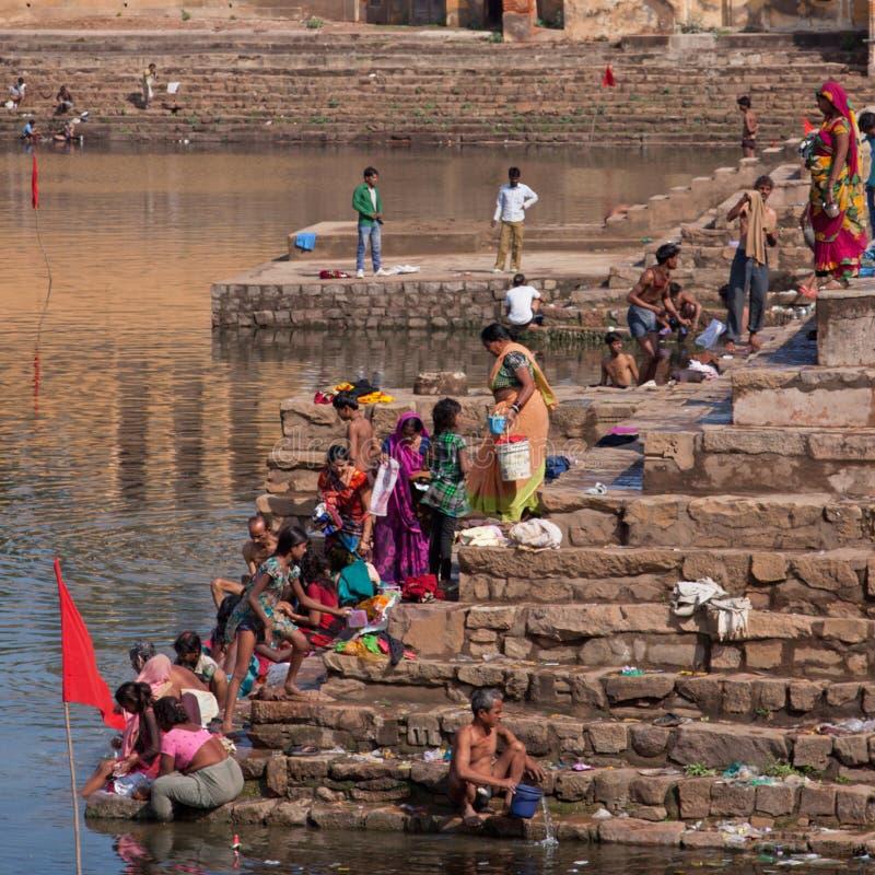 Badning och tvagning på den lokala ghaten på Khajuraho, Indien arkivbild