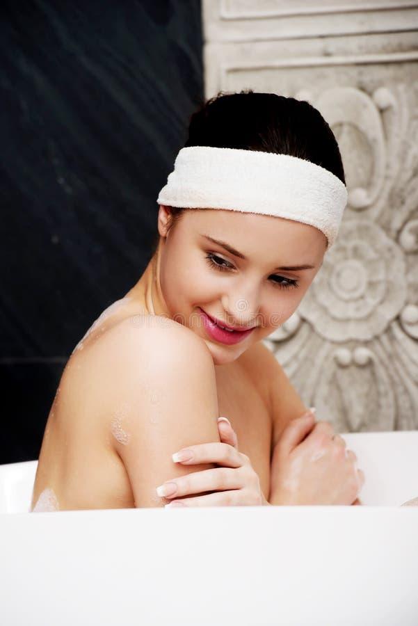 Badningkvinna som kopplar av i bad royaltyfri bild