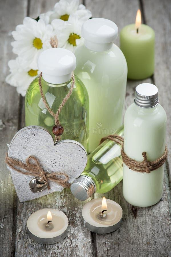 Badprodukte, Kerzen, hölzerner Hintergrund lizenzfreie stockbilder