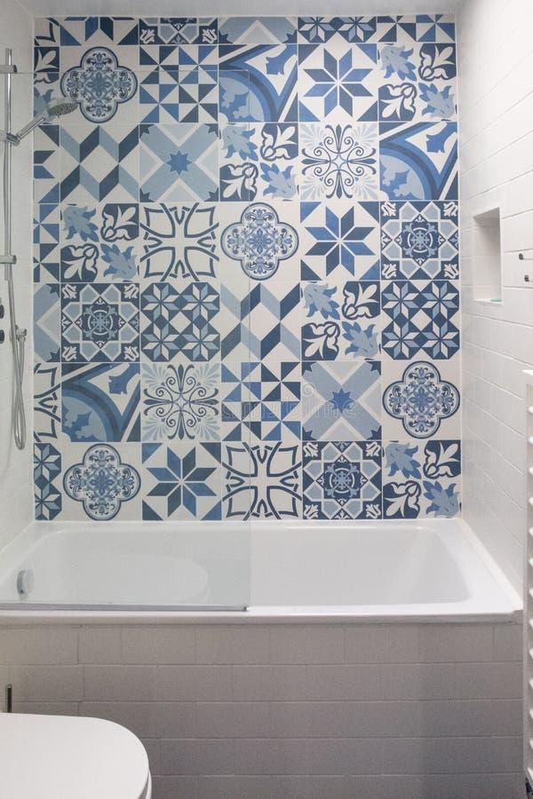 Badrum med badet, toalett, nisch i vägg- och handfatenheten, med blåa och vita patchworktegelplattor ovanför badet arkivbilder