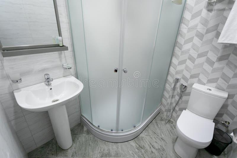 Badrum med tegelplattor och ljusa färger av kvasten, dusch med frostade dörrar, spegel ovanför vasken Hänga en handduk över toale arkivfoto